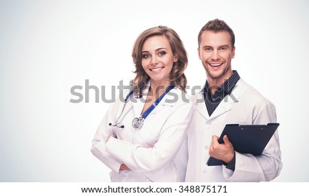 Friendly Handsome Smiling Male and Female Doctors On Blue Gradient Background With Copyspace - stock photo
