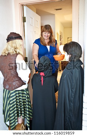Friendly home owner passing out Halloween candy to neighborhood trick-or-treating children. - stock photo