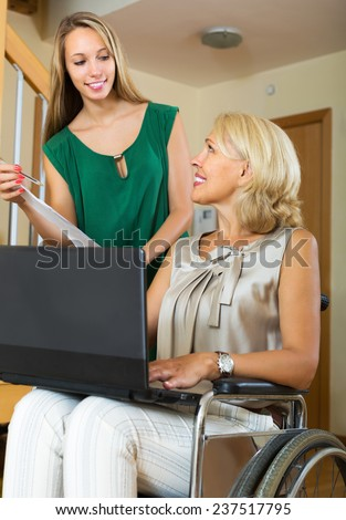 Friendly insurance agent and positive disabled woman on chair indoor