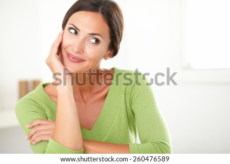 Friendly latin lady in green shirt smiling and looking satisfied to her left at home - copyspace - stock photo