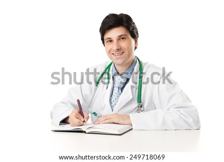 Friendly male doctor at the desk smiling. Isolated over white - stock photo