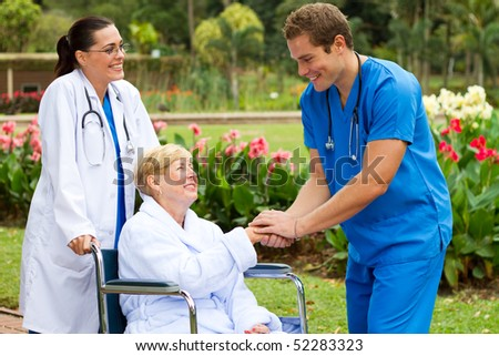 friendly male doctor greeting recovering senior patient in wheelchair outdoors - stock photo