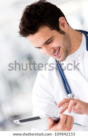 Friendly male doctor holding a tablet computer and smiling - stock photo