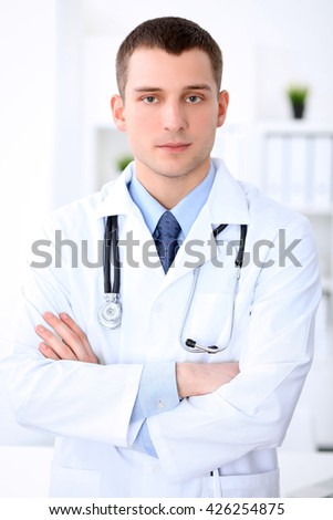Friendly male doctor in the hospital office. Ready to examine and help patients. High level and quality medical service concept.  - stock photo
