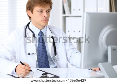 Friendly male doctor is sitting at the table and working in the hospital office. Ready to examine and help patients. High level and quality medical service concept. - stock photo
