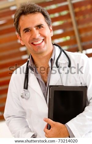Friendly male doctor smiling at the hospital - stock photo