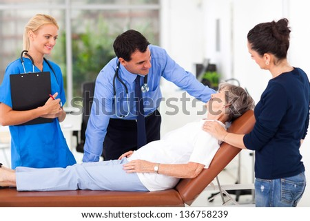 friendly male doctor talking to senior patient before examining - stock photo