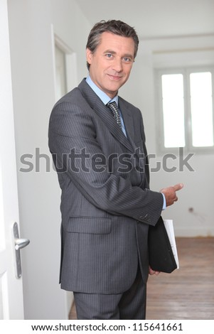 Friendly male estate-agent - stock photo