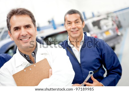 Friendly male mechanics at a car garage - stock photo