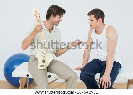 Friendly male physiotherapist explaining the spine to a patient in medical office - stock photo