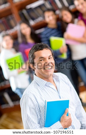 Friendly male teacher with a group of students smiling - stock photo
