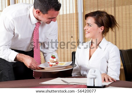friendly male waiter brings to the customer the ordered dessert - stock photo