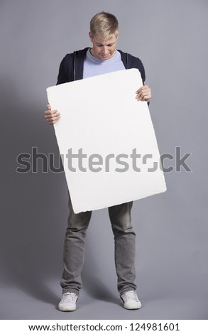 Friendly man looking at white empty signboard with space for text while holding it, isolated on grey background. - stock photo