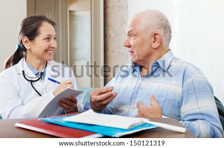 friendly mature doctor talks with joyful senior man at hospital