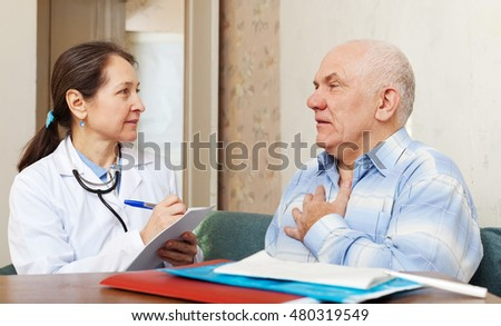 friendly mature doctor talks with sick senior man at near table