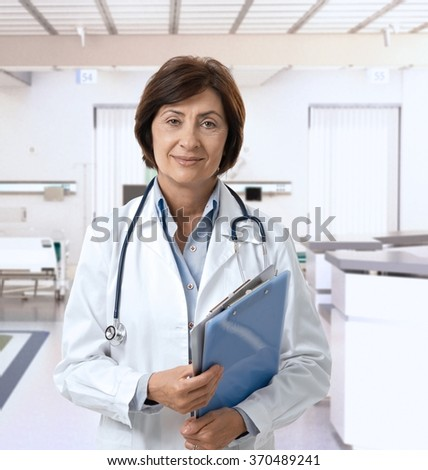 Friendly mature female doctor at hospital smiling.
