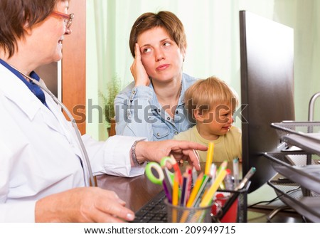 Friendly mature  female pediatrician doctor at the table examining toddler at clinic office - stock photo
