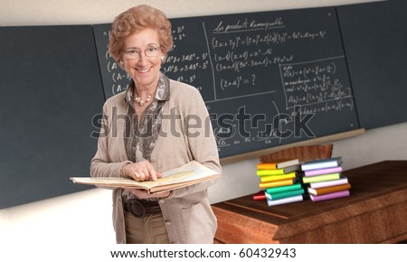 Friendly mature teacher pointing to a book in a classroom - stock photo