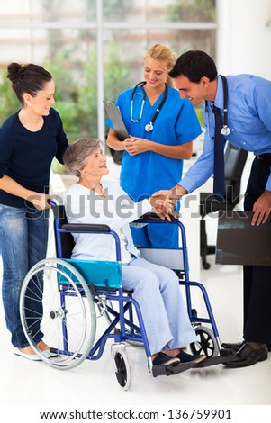 friendly medical doctor handshaking with senior patient - stock photo
