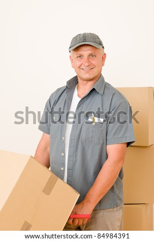 Friendly messenger or mover delivering parcel boxes on hand truck - stock photo