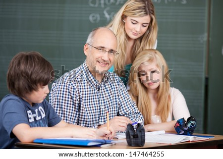Friendly middle-aged male teacher sitting at a desk with class notes surrounded by his young pupils, two attractive teenage girls and a boy - stock photo