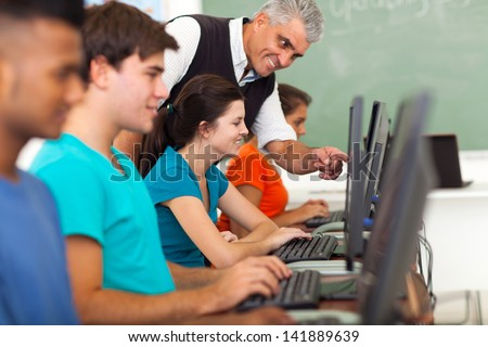 friendly middle aged teacher teaching computer to high school students - stock photo