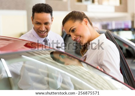 friendly middle aged vehicle dealer showing young woman new car - stock photo