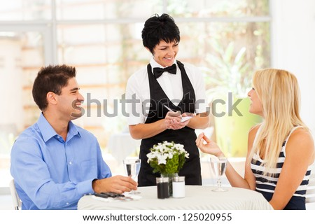 friendly middle aged waitress taking order from customer in restaurant - stock photo