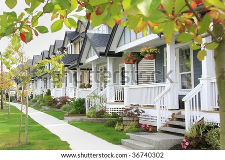 Friendly neighborhood with porches and sidewalk. - stock photo