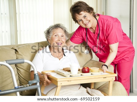 Friendly nurse brings a mean to an elderly shut-in.  Could also be lunch time at the nursing home. - stock photo