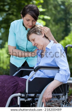 Friendly nurse comforting an old woman on wheelchair - stock photo