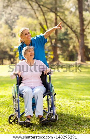 friendly nurse taking disabled elderly patient for a walk  - stock photo