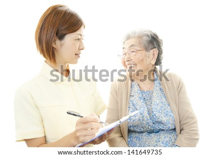 Friendly nurse with elderly woman - stock photo