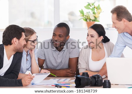 Friendly office discussion. Group of cheerful business people sitting together at the table and discussing something - stock photo
