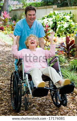 Friendly orderly and senior lady having great fun as he pushes her wheelchair. - stock photo