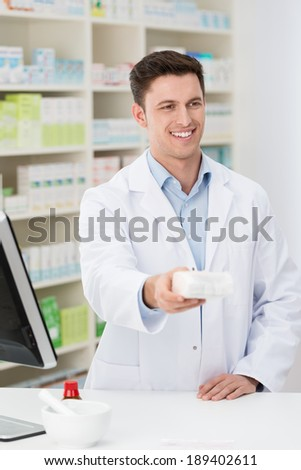 Friendly pharmacist dispensing a prescription handing over the box of medication to a patient with a smile - stock photo