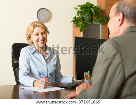 Friendly public notary helping senior client to make a will - stock photo