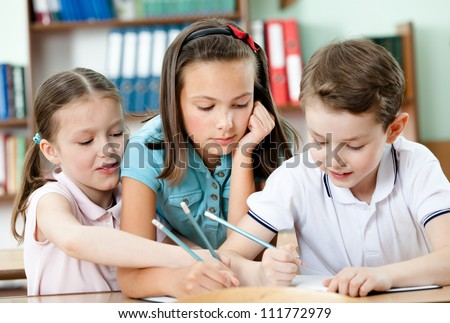 Friendly pupils help to each other - stock photo