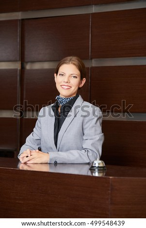 Friendly receptionist at hotel reception smiling