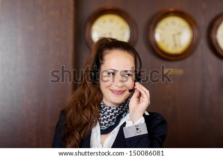 Friendly receptionist wearing a headset listening to a call while giving a beautiful smile - stock photo
