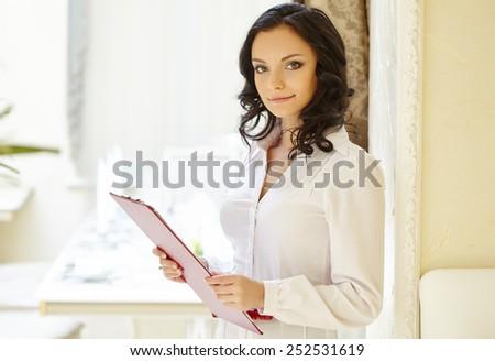 Friendly restaurant hostess posing at camera - stock photo