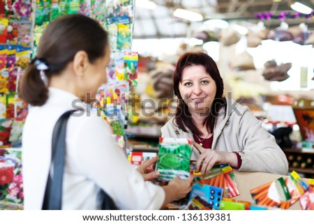 friendly saleswoman and  byer with seeds in market - stock photo