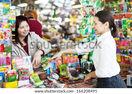 friendly saleswoman and mature woman with seeds at shop for gardener - stock photo