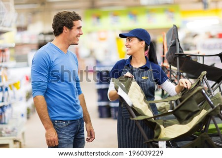 friendly saleswoman selling camping chair to customer in supermarket - stock photo