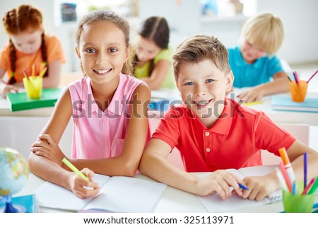 Friendly schoolchildren looking at camera while sitting by desk - stock photo