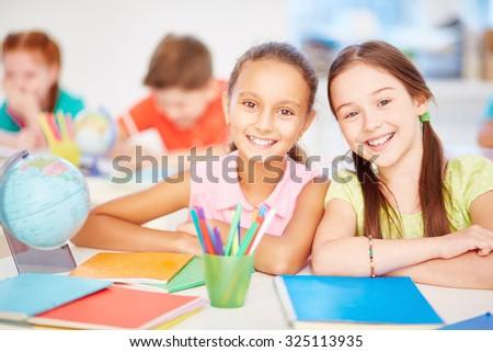 Friendly schoolgirls looking at camera in school - stock photo