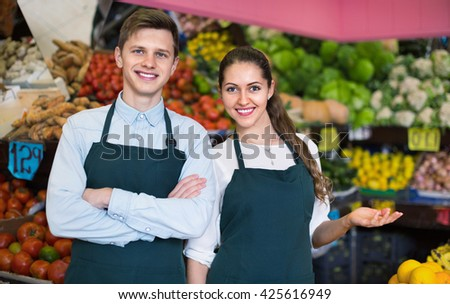 Friendly sellers having vegetables and fruits on displays of market