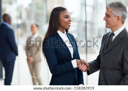 friendly senior businessman handshaking with young businesswoman in office - stock photo