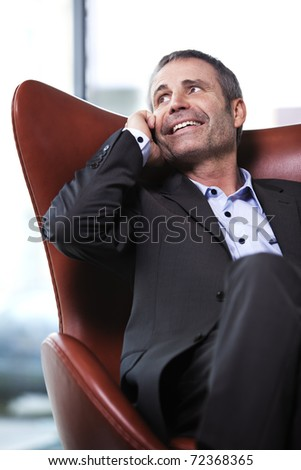 Friendly senior businessman in grey suit sitting on red chair and talking on mobile-phone. - stock photo