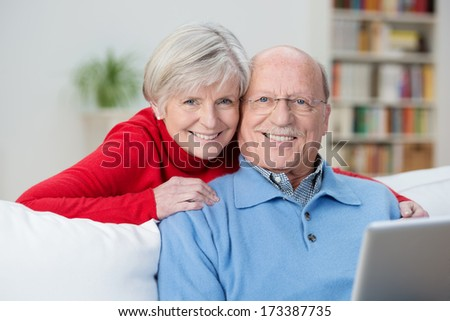 Friendly senior couple with happy contented smiles posing together in their living room with the husband sitting using a tablet on the sofa as his wife hugs him from behind - stock photo
